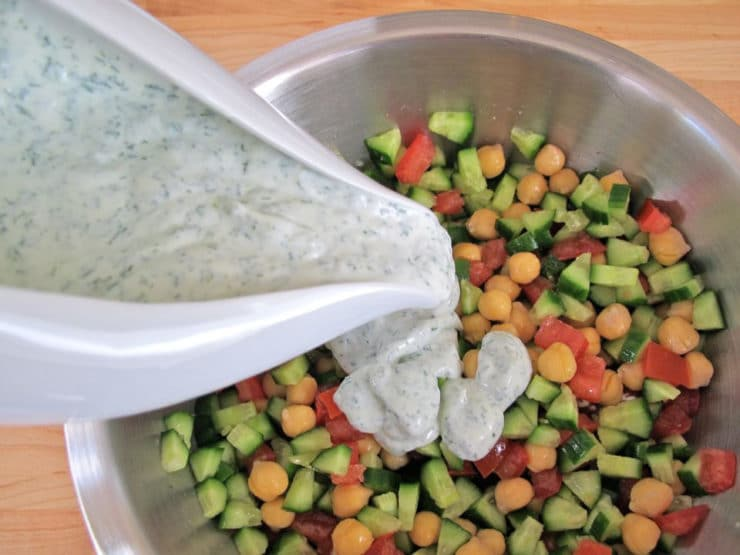 Pouring dressing over chickpea salad.
