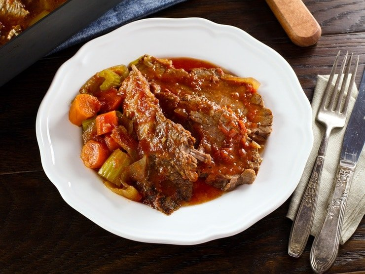 Overhead view of a slice of beef brisket next to a side of vegetables and topped with gravy on a round white plate.