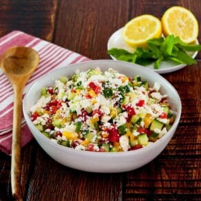 Square crop - bowl filled with fresh Israeli Salad with Feta, tomatoes, cucumbers and bell peppers. Mint and lemon in the background, cloth napkin and wooden spoon beside the bowl.