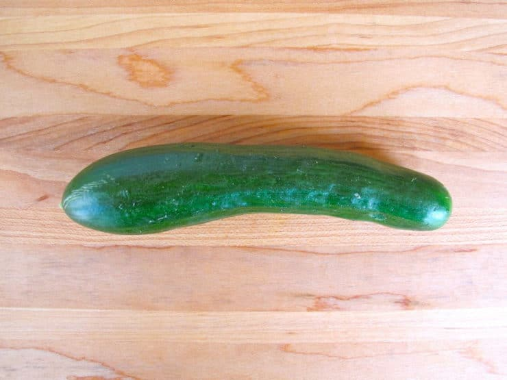 Persian cucumber on wooden cutting board.
