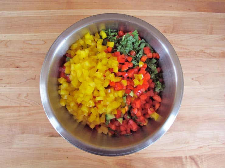 Diced bell peppers and mint in a large mixing bowl.
