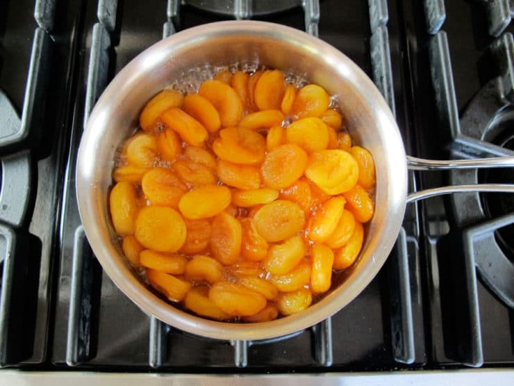 Dried apricots simmering in a saucepan.