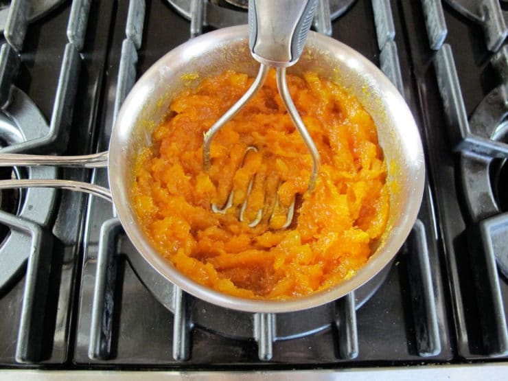 Using a potato masher on simmered apricots.