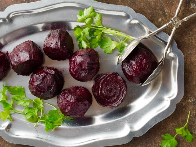 Roasted beets with parsley on silver tray with antique silver tongs.