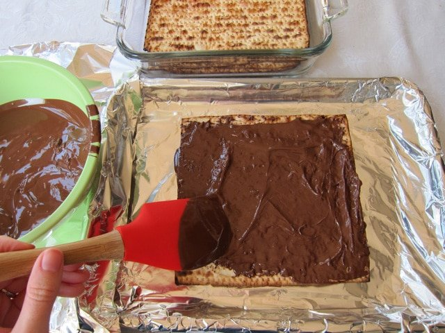Spreading melted chocolate on matzo.
