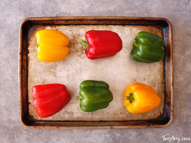 Colorful bell peppers on baking sheet.