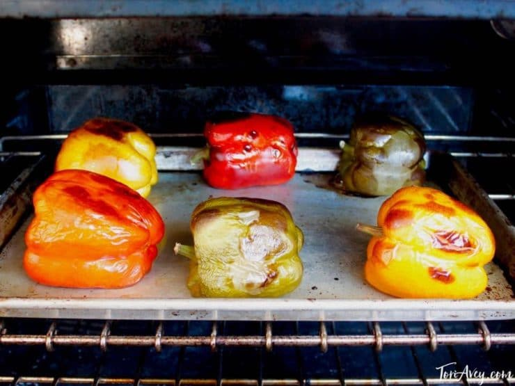 Colorful bell peppers blackened on baking sheet.