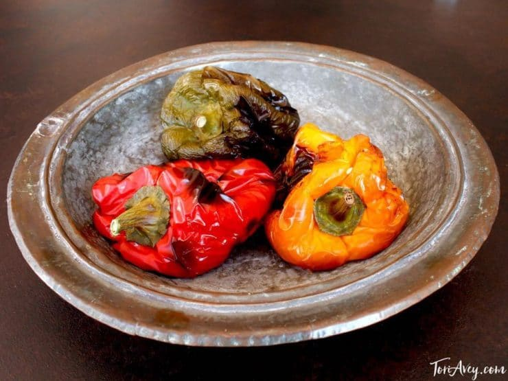 Green, red and yellow roasted bell peppers in silver bowl.