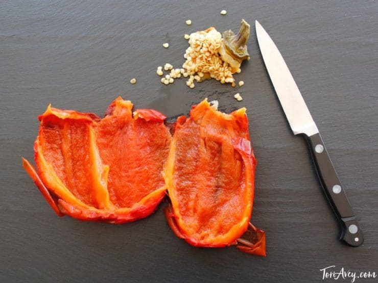 Roasted seeded red bell pepper on cutting board.