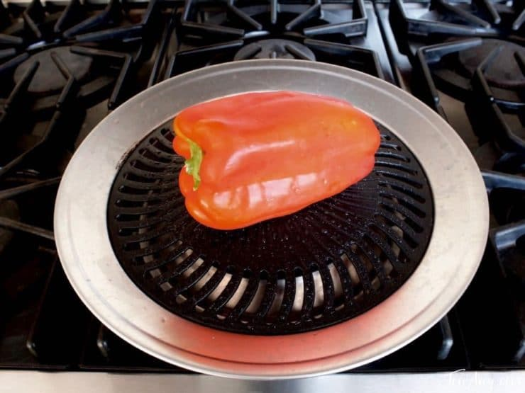 Red bell pepper roasting on grill pan.
