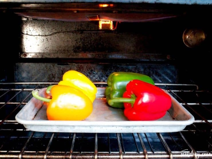 Colorful bell peppers on baking sheet under broiler.