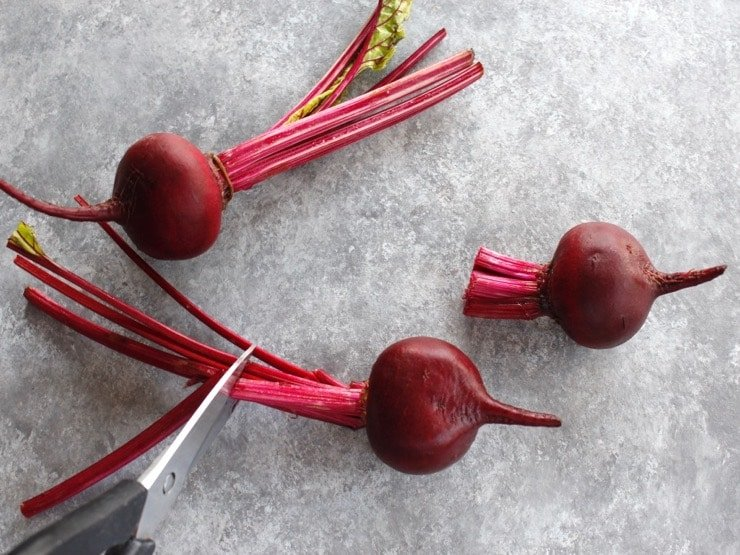 Three beets, with stems being trimmed by kitchen shears, on grey concrete background.