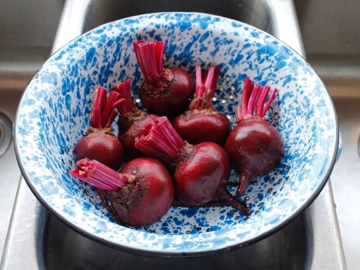 Clean scrubbed beets in blue speckled colander in stainless steel sink.