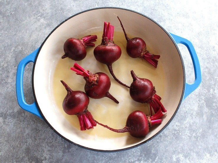 7 beets in a blue and white enamel cast iron casserole dish on a grey concrete background.