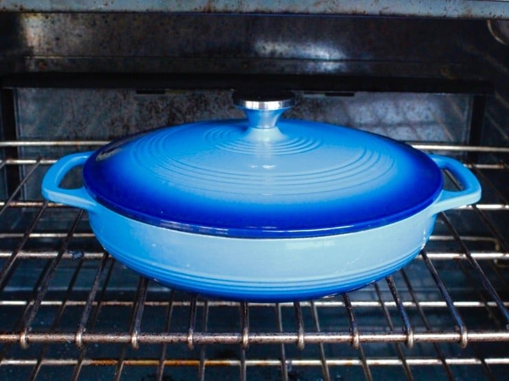 Blue cast iron casserole dish in oven.