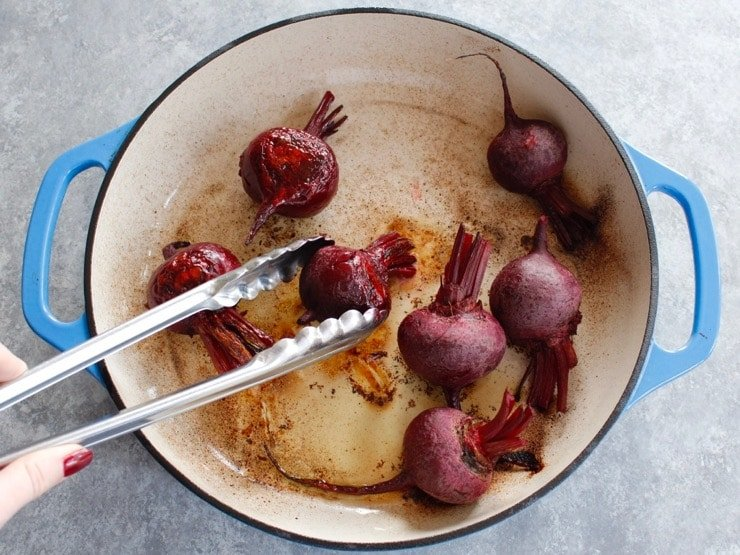 Flipping half-cooked beets in enameled casserole dish with stainless tongs on a concrete background.