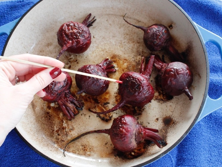 Hand skewering a roasted beet with a wooden skewer in an enameled cast iron casserole dish on a blue towel.