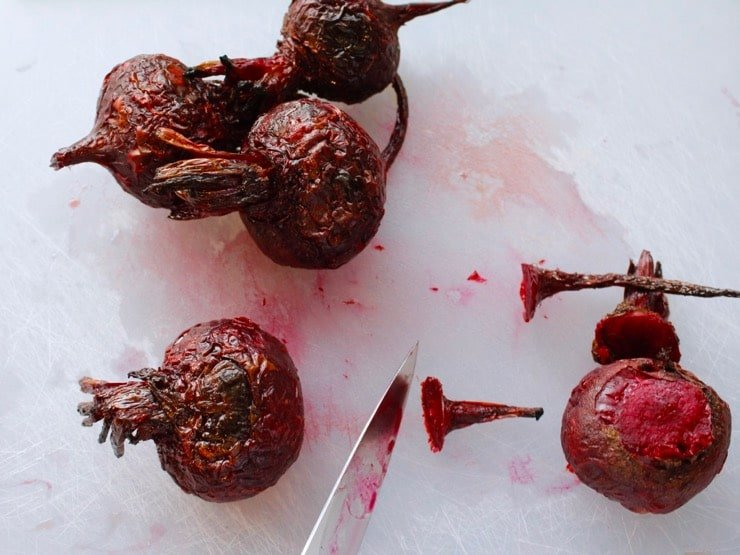 Chef's knife slicing tops and tips from roasted beets on a white cutting board.