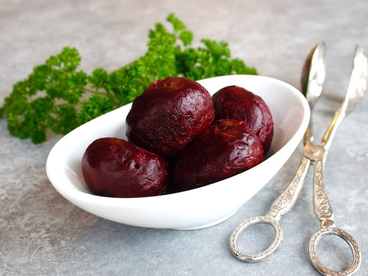 Roasted peeled beets in a white bowl with fresh parsley and antique silver tongs.
