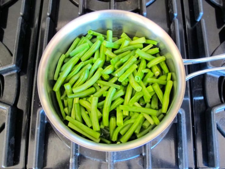 Blanching green beans in a saucepan.