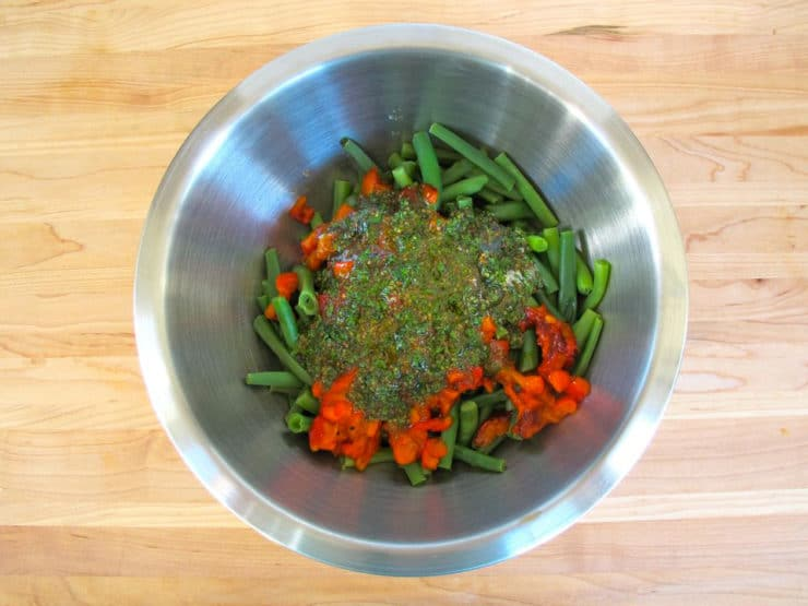 Dressing poured over green beans in a mixing bowl.
