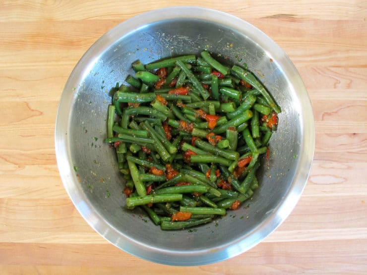 Green beans tossed with dressing in a bowl.