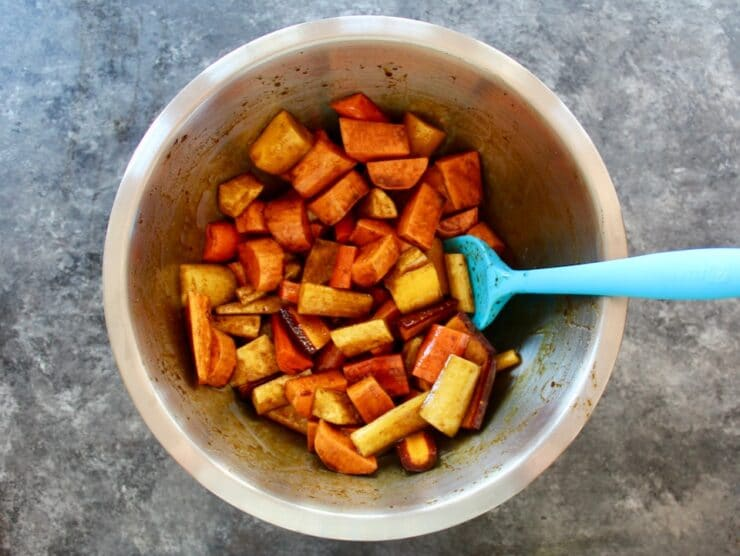 Bowl of root vegetables cut up tossed with molasses and olive oil, blue spatula, on concrete background.
