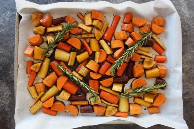 Cut up root vegetables on parchment-lined baking sheet with rosemary sprigs.