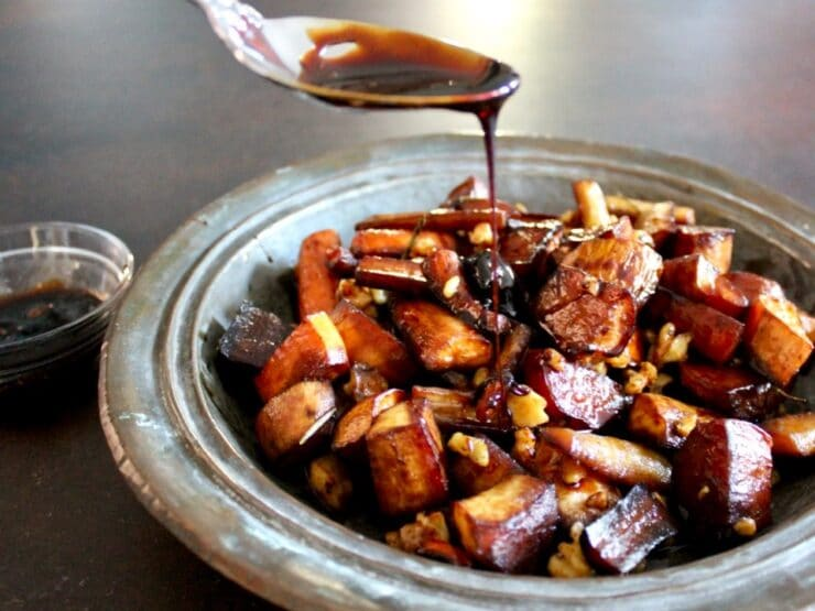 Spoon drizzling balsamic reduction onto roasted root vegetables and walnuts