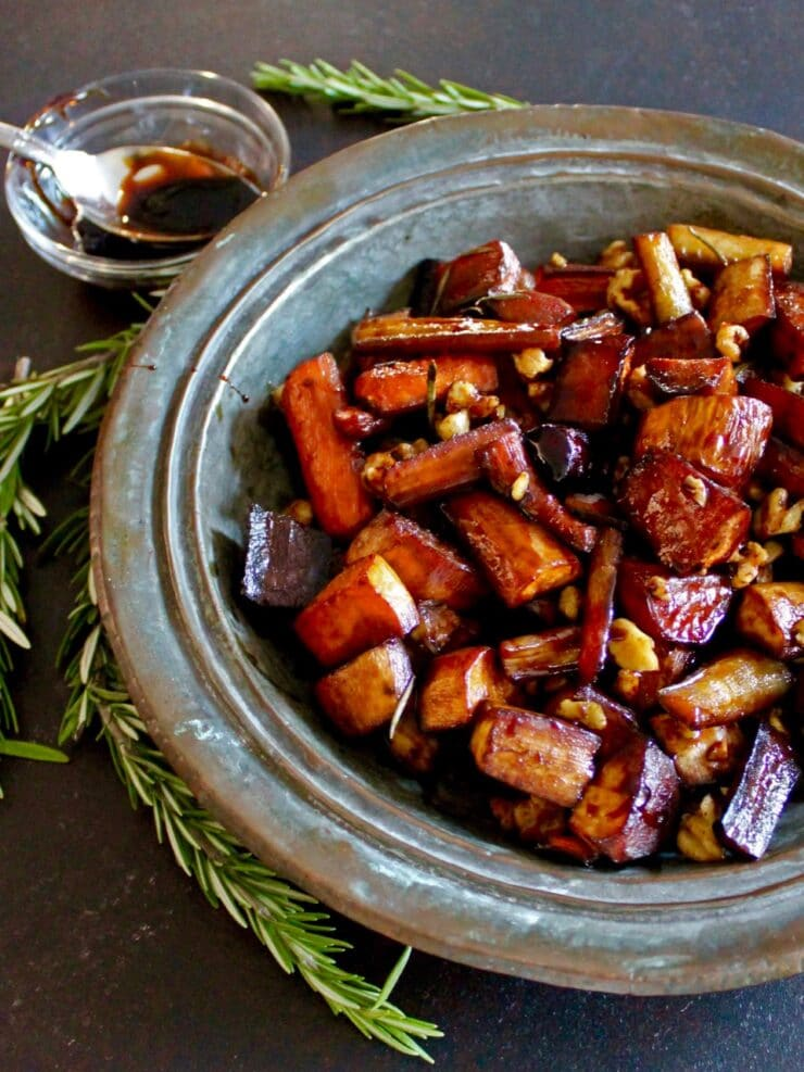 Roasted root vegetables on rustic metal platter, bowl of balsamic reduction in background, rosemary springs scattered around
