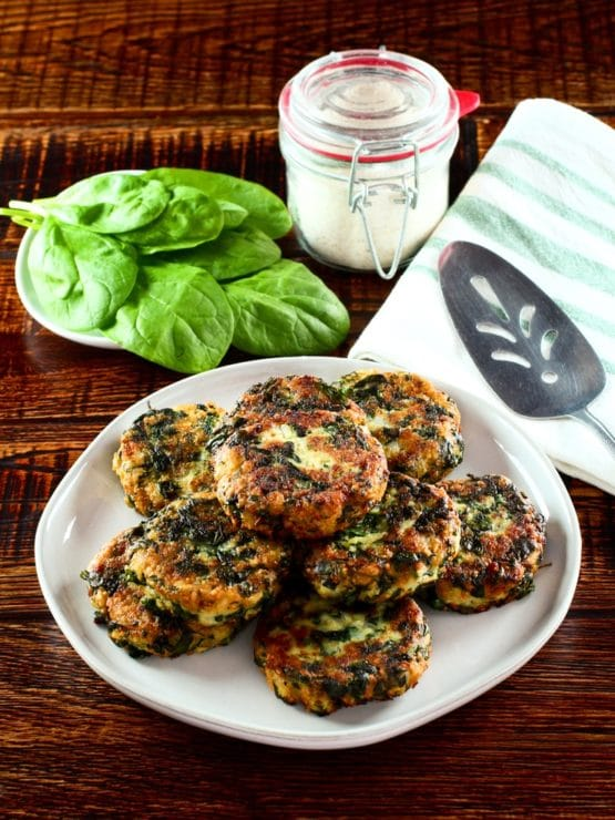 Plate of spinach keftes piled on a white plate with fresh spinach, canister of breadcrumbs, spatula and cloth napkin in background.