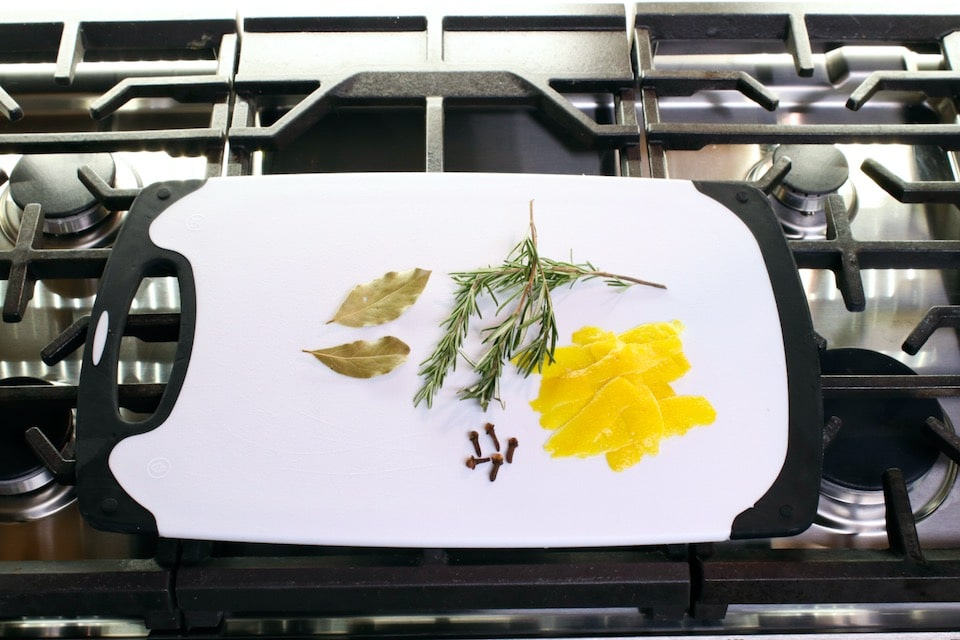 Ingredients for herb bundle on cutting board on stovetop - bay leaves, rosemary, cloves, lemon peel.