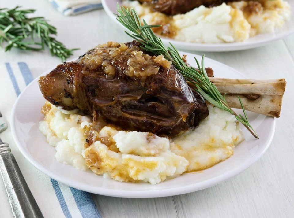 Frontal horizontal shot. Tender slow braised lamb shank on mashed potatoes with sprig of rosemary on a white plate, blue and white cloth napkin and fork on white table beneath. Another plate with shank and a sprig of rosemary in background.