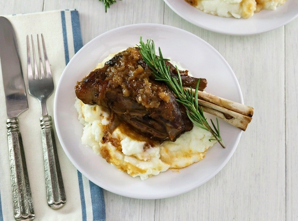 Overhead shot. Braised lamb shank on mashed potatoes with sprig of rosemary on a white plate, blue and white cloth napkin and fork on white table beneath.