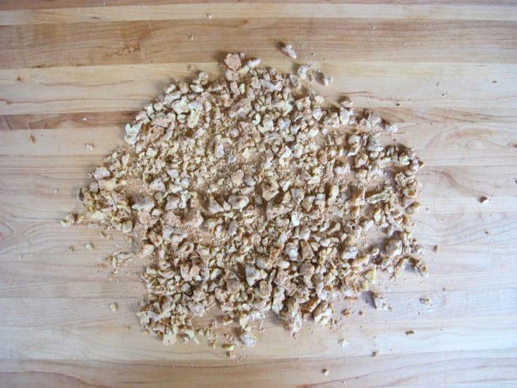 Roughly chopped walnuts on a cutting board.