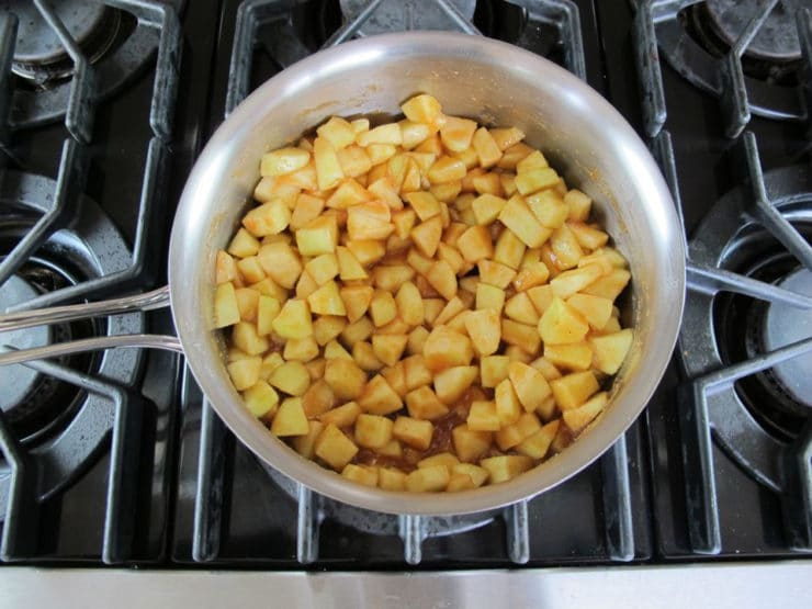 Diced apples simmering in a saucepan.