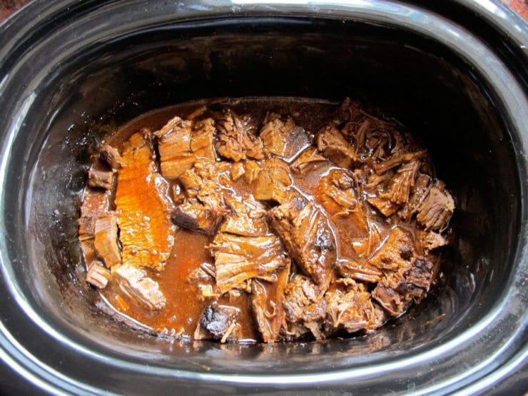 Sliced beef brisket returned to the slow cooker.