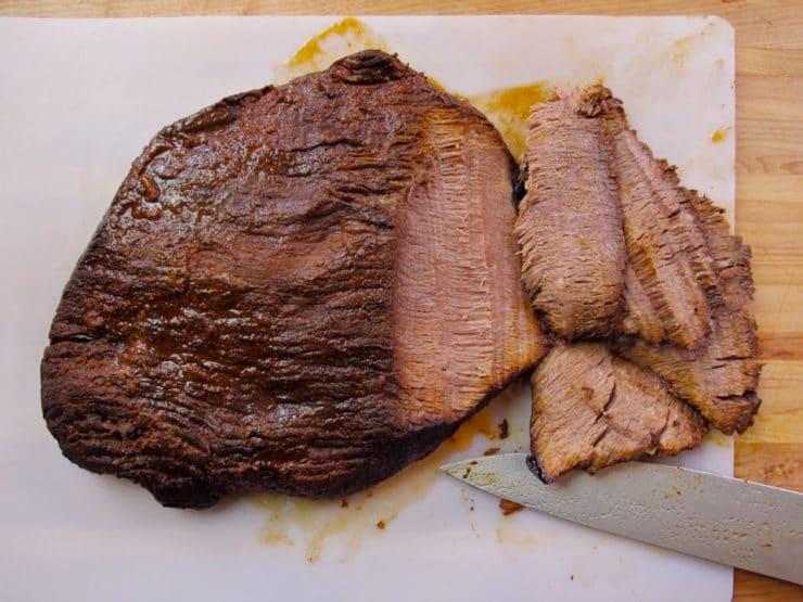 Slicing beef brisket against the grain.