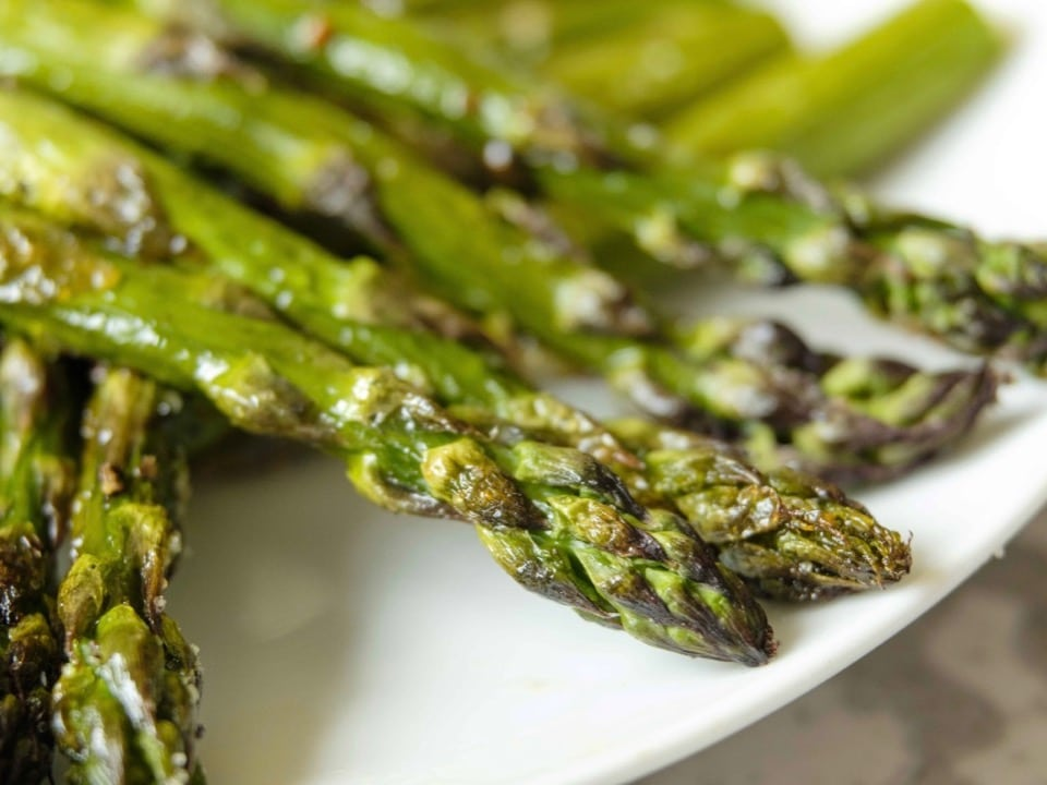 Close up of crisp roasted asparagus tips piled on a white plate.