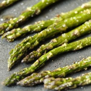 Close up of crisp roasted asparagus tips lined up on a baking sheet with salt.