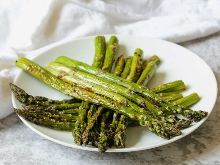Three small piles of aligned roasted asparagus criss-crossed diagonally on a white plate, linen napkin in background.
