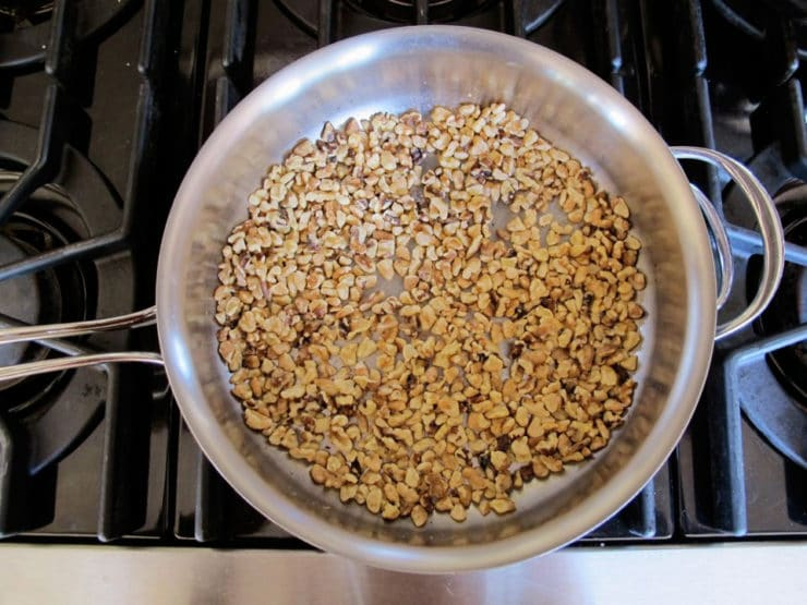 Chopped walnuts toasting in a pan.
