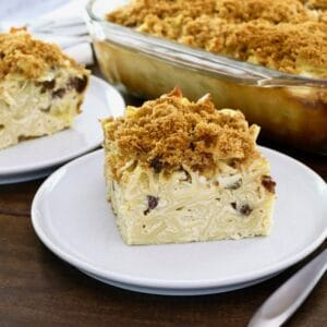 Horizontal Crop - close up of a slice of creamy noodle kugel with raisins and pineapples, with fork beside it, on wooden table. Baking dish of kugel and another slice in background.