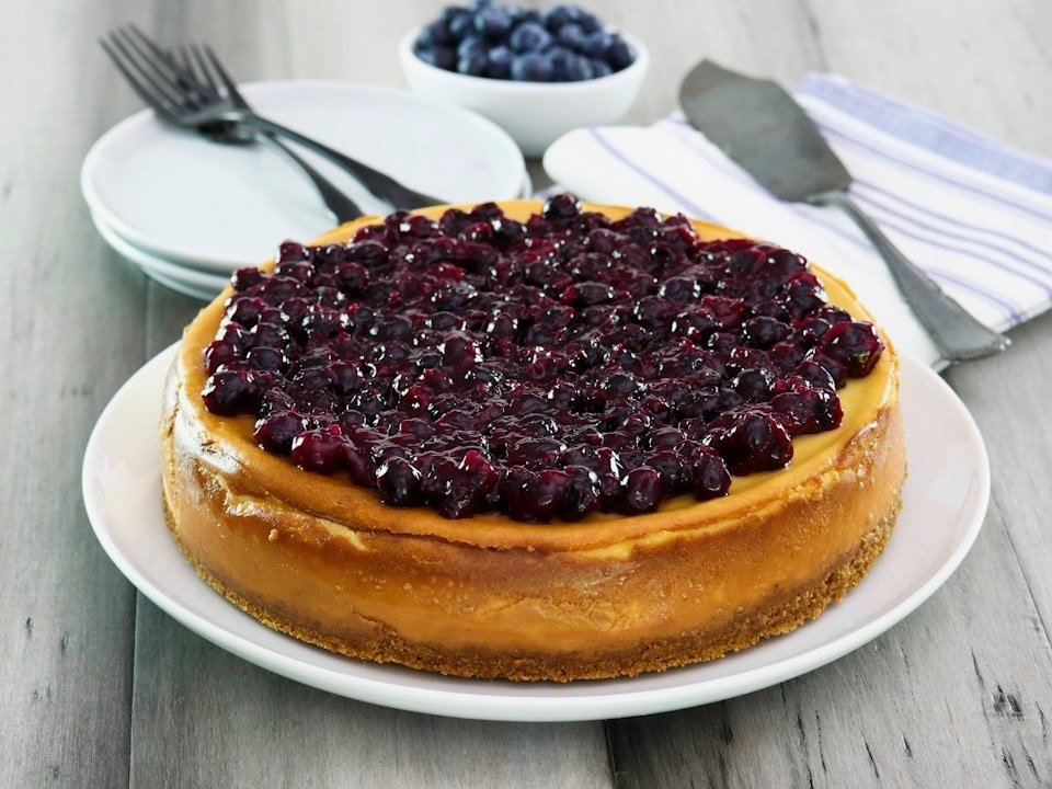 Cheesecake whole on plate, topped with thick rich blueberry topping with fresh blueberries in background. Utensils and plates behind.