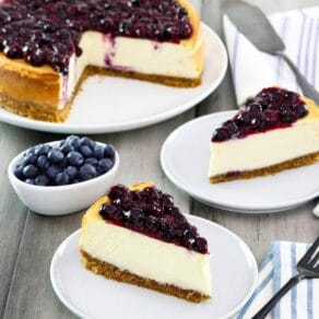 Square crop - two slices of cheesecake on plates with fresh blueberries beside them, a whole cheesecake with slices cut out and pie server in background.