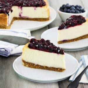Horizontal crop - two slices of cheesecake on plates with fresh blueberries beside them, a whole cheesecake with slices cut out and pie server in background.