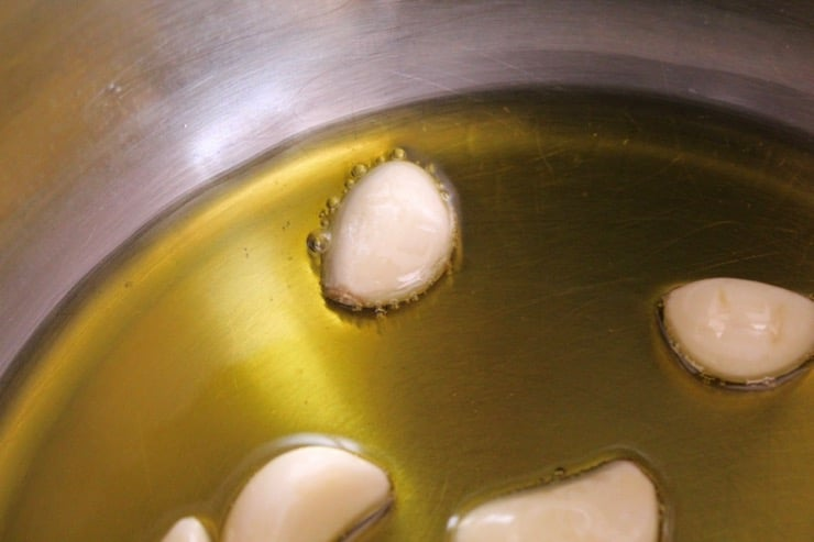 Garlic clove in pan of olive oil, sizzling around the edges of the clove.