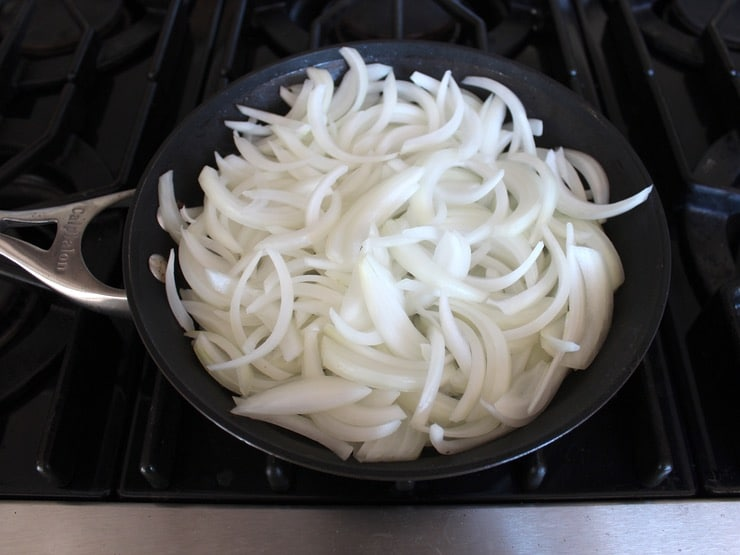Large skillet full of uncooked sliced onions on stovetop.