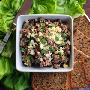 Horizontal shot - dish of chopped liver garnished with chopped hard boiled egg and fresh parsley, with lettuce, serving knife and rye bread pieces, on a wooden cutting board.