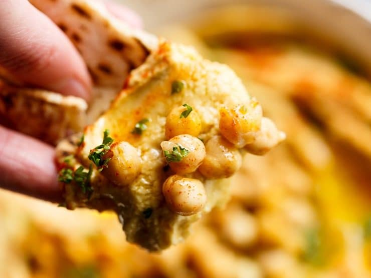 Close up of hand dipping piece of pita bread into hummus with whole chickpeas and fresh parsley garnish.